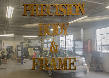 Precision Body & Frame interior sign with garage view